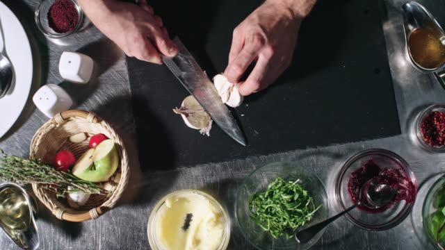 Cook Cutting Garlic Cloves in Kitchen video