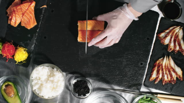 Cook Cutting Sushi Rolls for Serving video