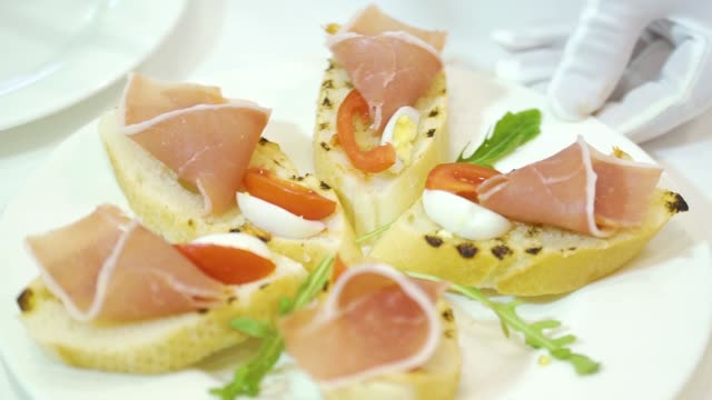 A cook decorates a ceramic plate of sandwiches made of cured meat, cherry tomatoes and quail eggs, laying green cilantro leaves between them. A cook decorates a ceramic plate of sandwiches made of cured meat, cherry tomatoes and quail eggs, laying green cilantro leaves between them. Serving of dishes. Close-up. jerky stock videos & royalty-free footage