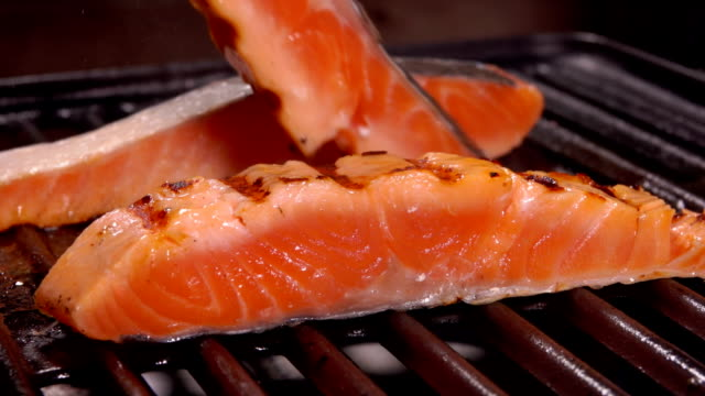Cook flips a raw salmon with metal tongs on grill - video