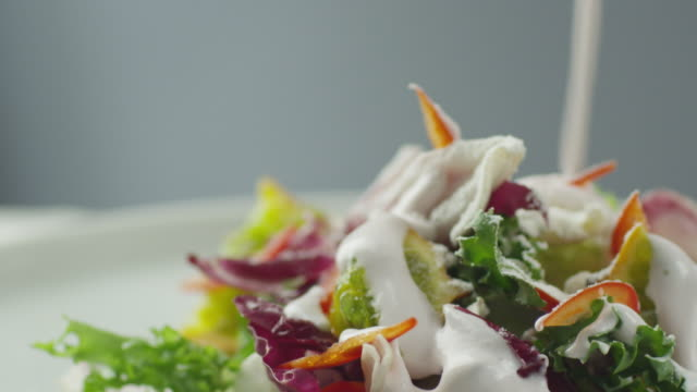 cook garnishing vegetable salad with sour cream - insalata video stock e b–roll