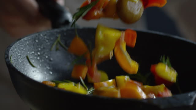 Cook Griddling Vegetables in Skillet Close up of male hand holding pan and mixing frying vegetables by pan shaking frying pan stock videos & royalty-free footage