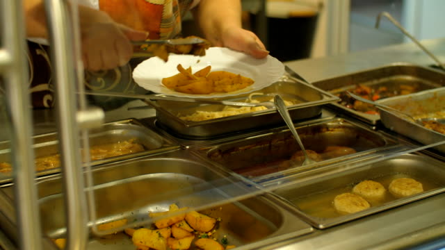 Cook in a canteen puts potatoes Cook in a canteen puts potatoes in a plate cafeteria stock videos & royalty-free footage