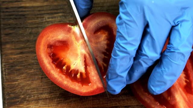 Cook in gloves cuts half tomato in kitchen of restaurant video
