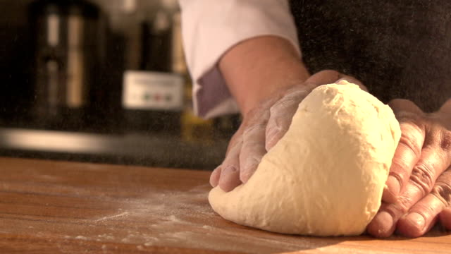 cook is making a cake. hands kneading dough in flour on table. Slow mo. Close-up video