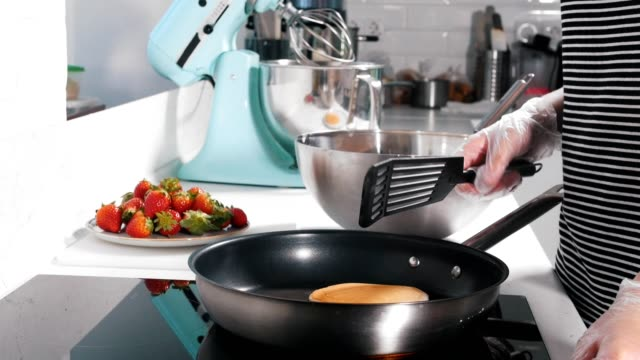 A cook is making pancakes in a pan