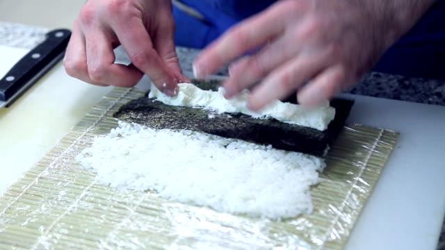 vídeos de stock, filmes e b-roll de cook fazer sushis, espalhando arroz em nori vídeo em hd - comida salgada
