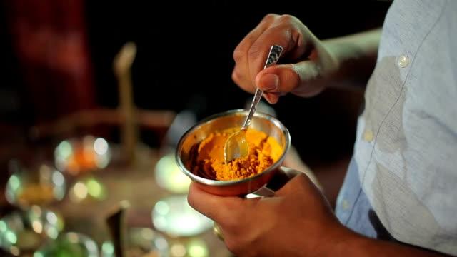 Cocinero mezcla con cuchara las especias en un tazón de fuente - vídeo