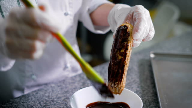 Cook pastry, in a white suit and gloves on his hands, smearing the melted chocolate yellow green silicone spatula on a freshly baked eclairs. Chocolate flows in a white bowl, which stands under eclair video