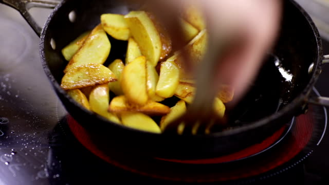 Cook potatoes in a frying pan Potatoes are fried in a frying pan in olive oil prepared potato stock videos & royalty-free footage