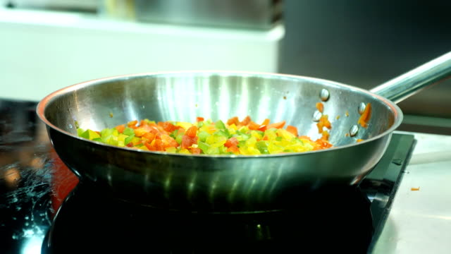 Cook pouring olive oil on vegetables in a frying pan. video