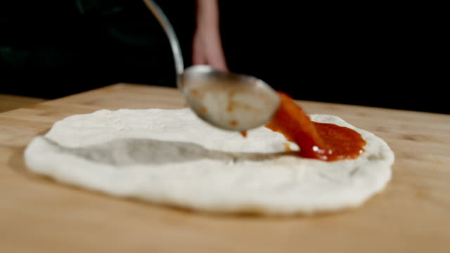 vídeos de stock e filmes b-roll de slo mo cook pouring tomato sauce over pizza dough - pizza