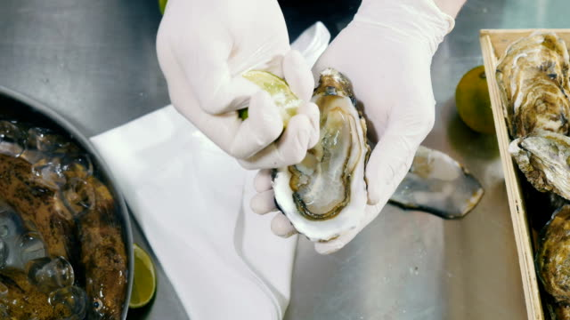 Cook pours the oyster with fresh lemon juice video
