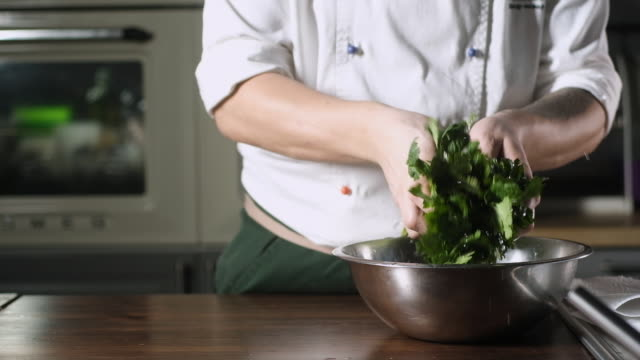 cook pulls parsley out of  water and shakes off the drops - chef triste video stock e b–roll