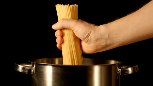 un cuoco mette in un casco di spaghetti in una pentola in acciaio - chef triste video stock e b–roll
