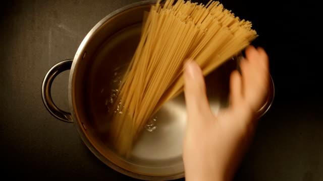 un cuoco mette in un spaghetti in una pentola in acciaio - chef triste video stock e b–roll