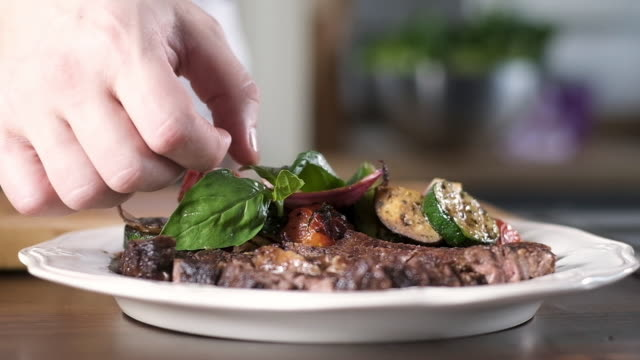 cook puts leaf basil on plate with slices of grilled beef and grilled vegetables - chef triste video stock e b–roll