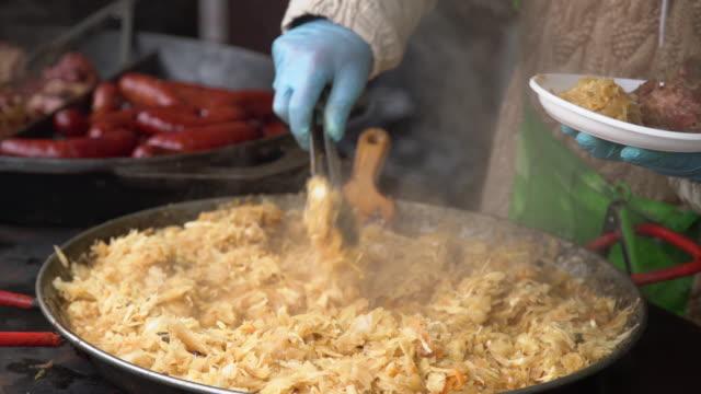 vídeos de stock, filmes e b-roll de cozinhe põr o repolho dourado stewed ao lado da carne de carne de porco na placa plástica para o costumer. alimento de rua para a venda em uma feira de cidade em europa - costumer