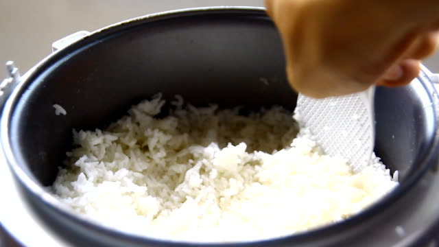 Cook rice in a pot on a wooden table with hand video