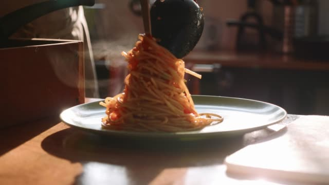 vídeos de stock e filmes b-roll de cook serving spaghetti on the plate - sauce tomatoes