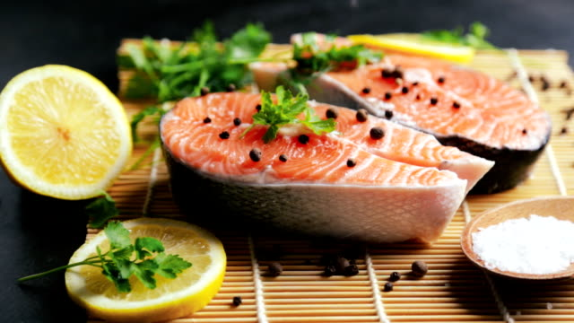cook sprinkles salmon steaks with salt - filetto video stock e b–roll