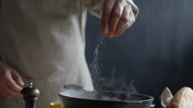 Cook Sprinkling Salt on Skillet Close up of chef hand adding salt to hot pan on stove spice stock videos & royalty-free footage