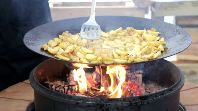 Cook stirred fried potatoes. Potatoes close - up which is fried on firewood, covered with smoke.