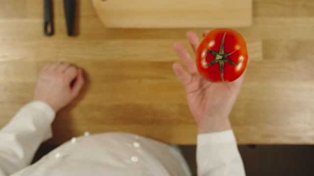 SLOW MOTION: Cook throws up tomato and catches it - Top View SLOW MOTION: Cook throws up tomato and catches it - Top View catching stock videos & royalty-free footage