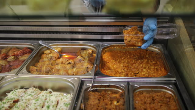 Cooked beans in steel trays with serving utensils in buffet. Bean soup