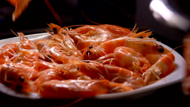 Cooked shrimps fall into a white plate - video