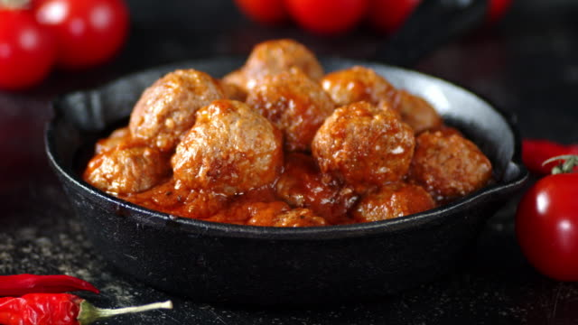 Cooked the meatballs in a frying pan slowly rotate. Cooked the meatballs in a frying pan slowly rotate. On a dark background. ground beef stock videos & royalty-free footage