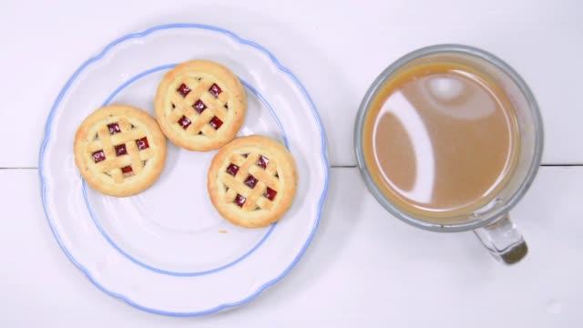 クッキーとコーヒーの時間の経過 - ソーサー点の映像素材/bロール
