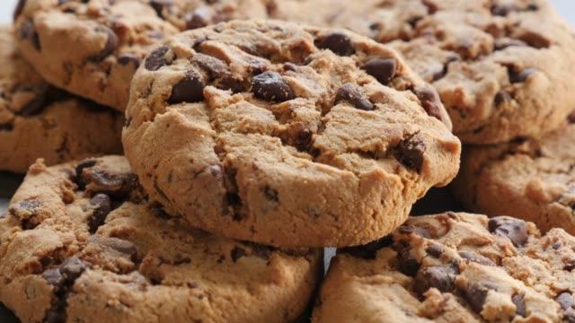vídeos de stock, filmes e b-roll de cookies na mesa de madeira lenta inclinação 4k 3840x2160 imagens ultrahd-slow tilt de biscoitos de chocolate em superfície de madeira 4k 2160p vídeo uhd - alimentação não saudável