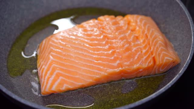 vídeos y material grabado en eventos de stock de cocinar un filete de salmón fresco en aceite de oliva - dieta paleolítica