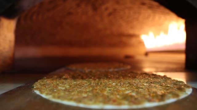kochen sie einen lahmacun kebab im brotbackofen. nahaufnahme. - döner stock-videos und b-roll-filmmaterial