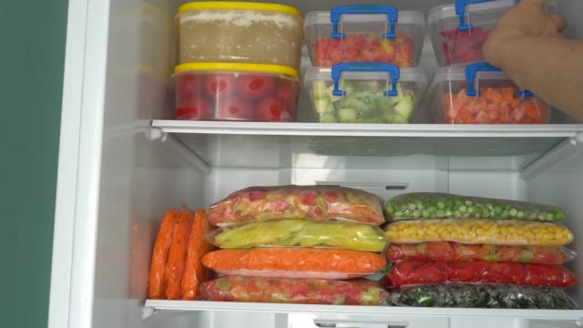 Cooking And Freezing Vegetables and Fruits Storage of Food in a Chest Freezer. Packages and containers with frozen meals freezer stock videos & royalty-free footage