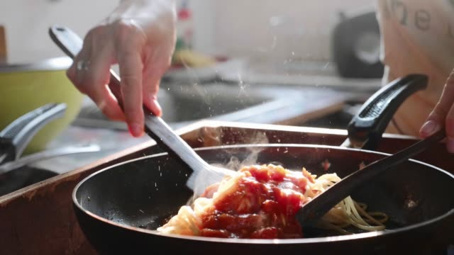 vídeos de stock e filmes b-roll de cooking and stirring the spaghetti with red tomato sauce in the frying pan. - sauce tomatoes