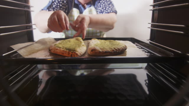 Cooking baked traditional italian pizza calzone in the oven Cooking baked traditional italian pizza calzone in the oven. Woman placing frozen stuffed pizza pockets on a baking sheet. View from inside of the electric oven. hot pockets stock videos & royalty-free footage
