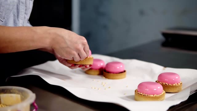 cooking, baking and confectionery concept - chef decorating mirror glaze cakes with golden sprinkles at kitchen - dolci video stock e b–roll