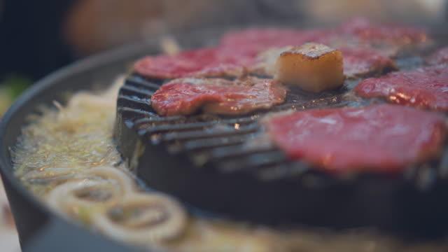 vídeos de stock, filmes e b-roll de cozinhar churrasco e grelhados no carvão no fogão. feche o bife grelhado no restaurante do japão. fatia de carne para churrasco ou comida estilo japonês - comida salgada