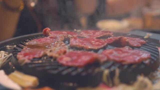 バーベキューを調理し、ストーブの上の炭火焼き。日本レストランでドネルケバブを閉じます。バーベキューや和風食品の牛肉スライス ビデオ