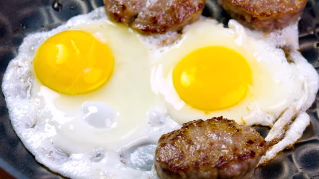 vídeos de stock, filmes e b-roll de culinária de café da manhã com ovos frescos e linguiça - salsicha