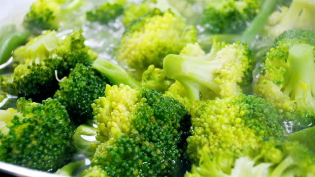 cucina broccoli e fagiolini in una padella. primo piano. - broccolo video stock e b–roll