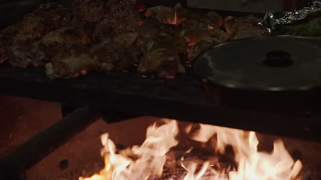 Cooking Chicken And Veggies On A Open Flame Fire Pit Grill With Cast Iron
