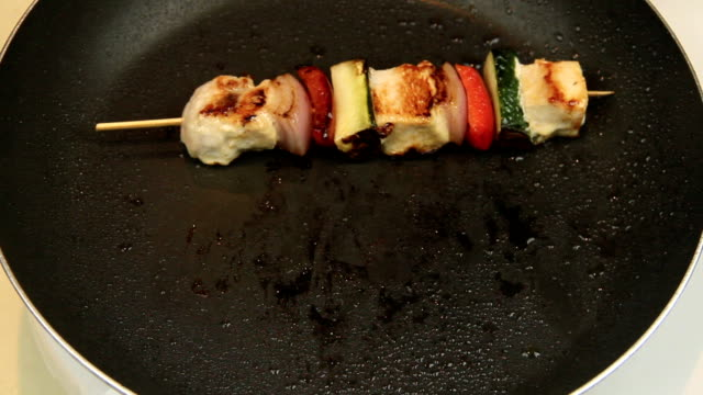 Cooking Chicken Kebabs 4 Serving chicken kebabs from a fry pan to a plate with salad. red onions stock videos & royalty-free footage