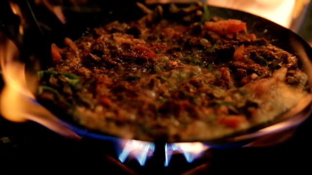 Cooking chopped meat in pan with flame