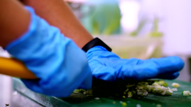 cooking. close-up, the chef, in protective gloves, is cutting green onion on cooking board. health food. safety concept. reopening canteen. volunteering and charity video