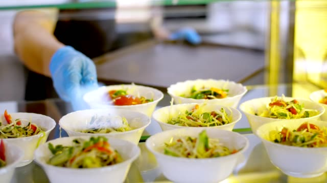 cooking. close-up. waiter, in protective gloves, puts bowls of salads to self-service food display showcase. Cuisine cafeteria buffet with food. health food. volunteering and charity. reopening . safety concept video