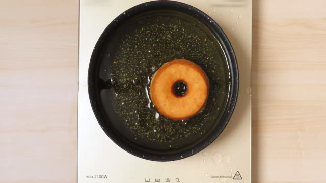 4K - Cooking deep-fried donut. Top view video