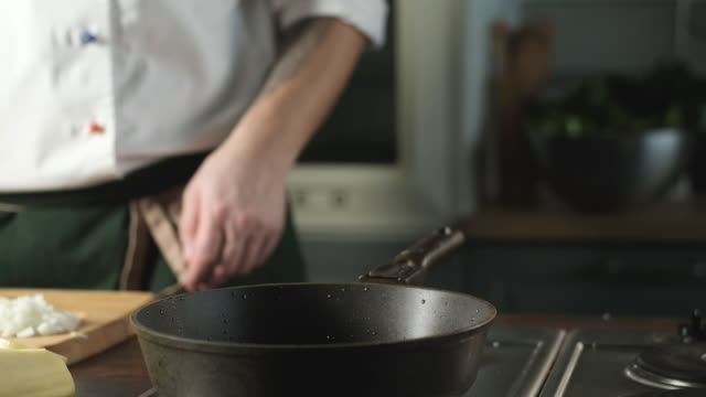 cooking delicious dish by chef in kitchen. man pours oil into frying pan. - chef triste video stock e b–roll